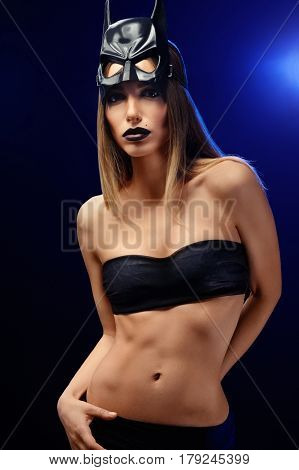 Fashion babe. Vertical shot of a young female fashion model with professional artistic makeup with black lipstick wearing batman mask and top showing off her toned body posing in artistic lighting