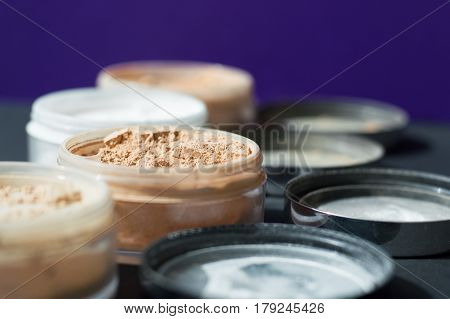 Mineral make up powder for matt skin. Variety of containers with beige and white powder for facial care. Focus on beige powder