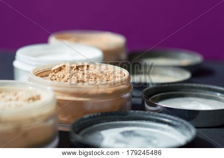 Mineral make up powder for matt skin. Variety of containers with beige and white powder for facial care. Focus on beige powder purple background