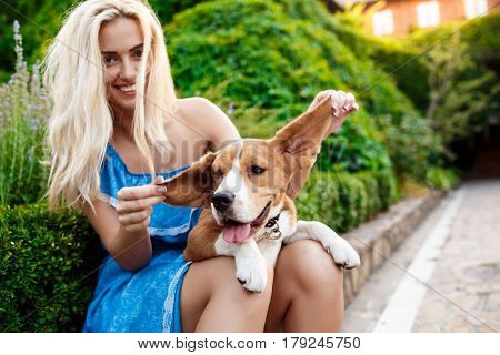 Young beautiful blonde girl in blue dress smiling, walking, playing with beagle dog in park.