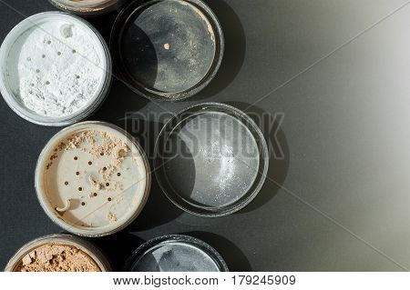 Background with mineral make-up powder for matt foundation of white and beige colors on black surface