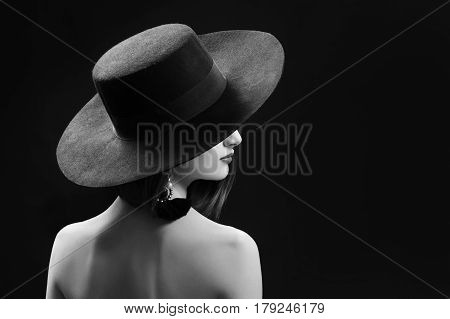 Black and white studio fashion portrait of an elegant female model posing on black background wearing wide hat hiding her face copyspace retro vintage old fashioned mysterious shadow concept.
