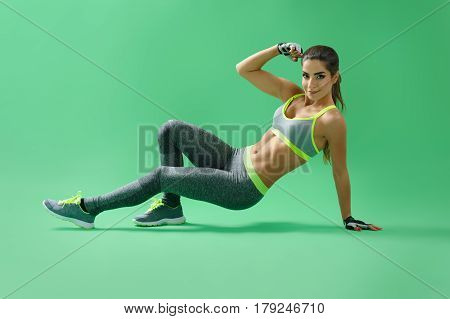 Getting powerful. Gorgeous young strong fit woman with athletic muscular body working out on green background body flexing fitness sports athletics activity hobby lifestyle trainer concept