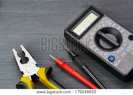 Multimeter And Pliers On A Dark Wooden Background.