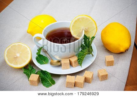 Tea with mint brown sugar and lemon on table