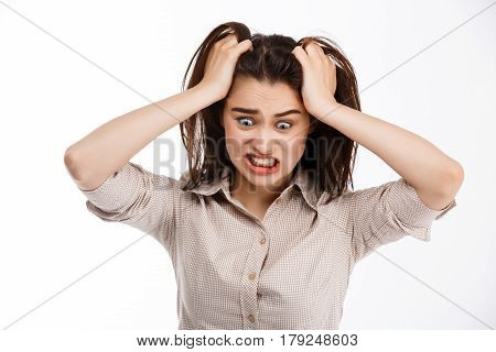 Young beautiful crazy brunette businessgirl clutching her head and screaming looking away over white background