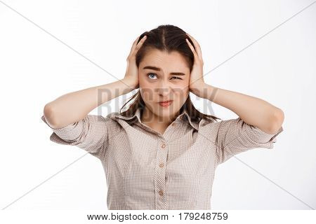 Young beautiful confused brunette businessgirl clutching her head looking up over white background