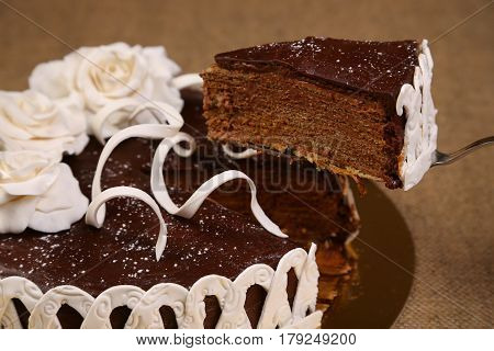 Piece of chocolate cake. White fondant flowers decoration. Bakery. Sweet food. Homemade cake.