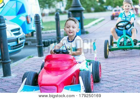 Smiling little boys driving by toy car