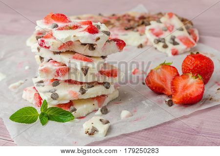 Homemade healthy frozen strawberry yogurt bark on rustic wooden background
