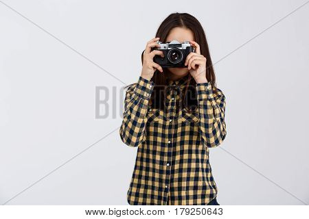 Young beautiful brunette photographer taking pictures, looking through viewfinder over white background.