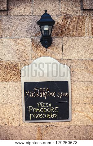 Commercial panel on the wall with written text that says that pizza is on the menu.