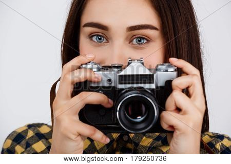 Close up portrait of young beautiful brunette photographer taking pictures, looking at camera over white background.