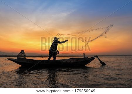 Silhouette Of Asian Fisherman On Wooden Boat In Action Throwing A Net For Catching Freshwater Fish I