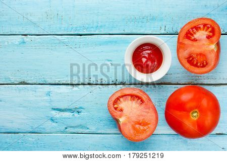 Fresh tomatoes and tomato sauce on blue wooden background top view blank space for text