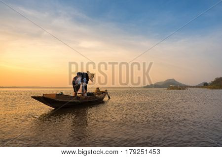 Asian Fisherman On Wooden Boat Preparing A Net For Catching Freshwater Fish In Nature River In The E