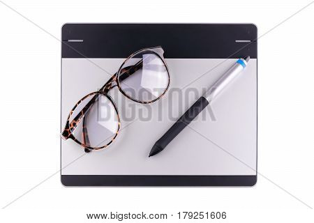 Top view of graphic tablet with pen and retro glass isolated on white background. For illustrators photographer and designers