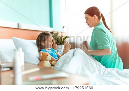 Doctor and little patient with teddy bear lying on bed in hospital