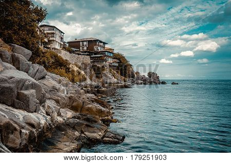houses on a rock cliff on seashore