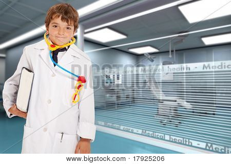 Young boy with a doctor?s uniform and toy stethoscope holding a book in a hospital interior