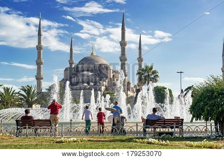ISTANBUL - MAY 24, 2013: Tourists admiring the view of the fountain and Blue Mosque (Sultanahmet Camii).