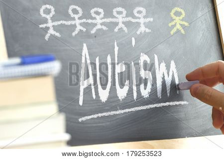 Hand writing on a blackboard in a class with the word AUTISM written on. Some books and school materials.