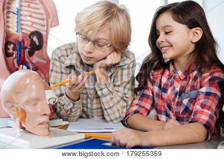 This is right hemisphere. Helping passionate little scientist explaining something to his fellow classmate while using a pencil pointing at human brain model