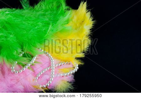 Colorful pink green yellow feathers and white perl necklace lay on black background. Space for text