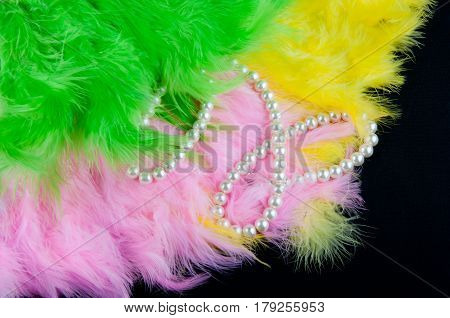 Green pink yellow folding fans made of feathers and perl necklace lay on black background