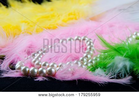 White perl necklace lay in green pink yellow white feathers and black table