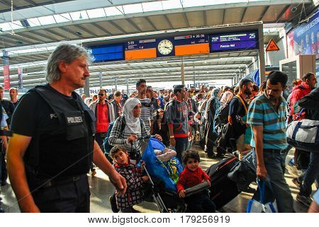Munich,Germany-September 12,2015:Police escort migrants arriving by train at Munich Central Station from the town of Passaufor further distribution to other cities and processing of their asylum aplications