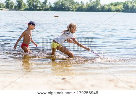 Children fishing in a river with a fishing net