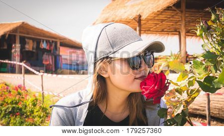 Asian women wearing caps and sunglasses are sniffing roses.