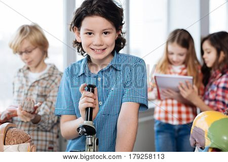 Learning interesting things. Vibrant talented clever kid holding a microspore and standing at the table while his classmates examining other interesting objects