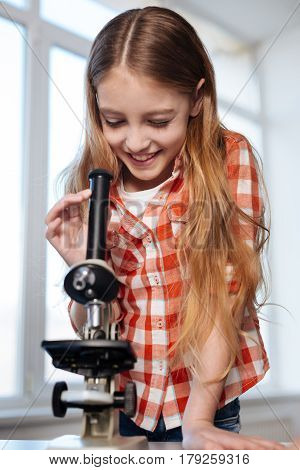 Little cells of life. Dedicated inspired intelligent girl examining bacteria while using a microscope for writing a research paper