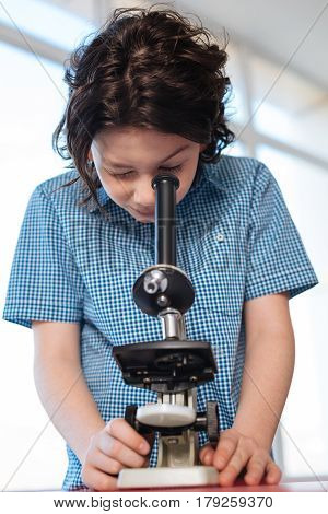 Looking for something peculiar. Focused observant passionate boy being precise using a microscope for studying some kind of bacteria in a lab