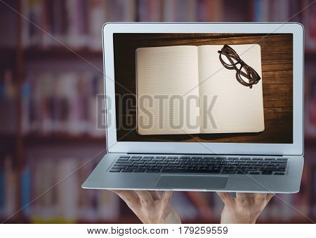 Digital composite of Hands with laptop showing open book and glasses against blurry bookshelf with purple overlay