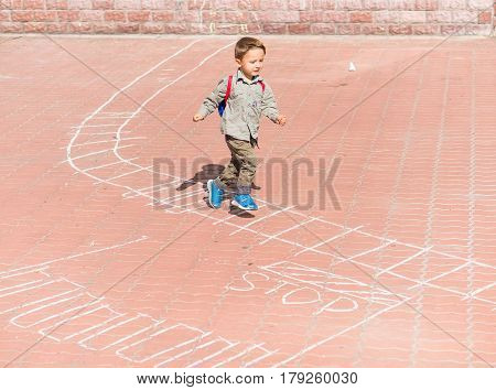 The boy runs to the drawings on the pavement. Cute kid boy drawing with chalk on the pavement in the park. Summer activities for children.