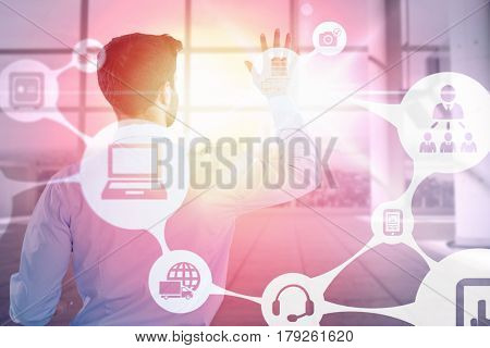 Rear view of businessman pretending to touch invisible screen against interior of empty office 3d