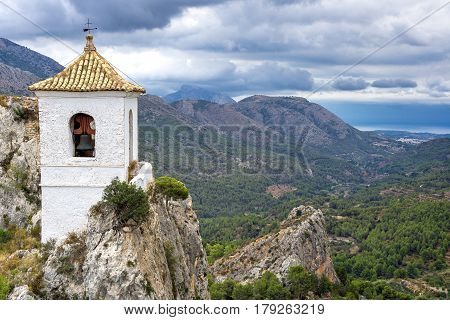 White bell tower. Landscape photo: View over the valleys of Puig Campana in the region of Alicante, Spain.