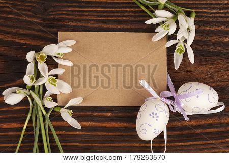 Traditional easter background with copyspace. Snowdrop flowers and easter eggs with blank label on brown wooden textured table.