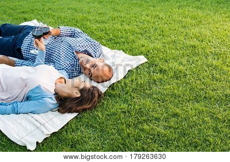 Mature happy couple lying down on grass raising a toast. Couple in park relaxing while drinking a glasses of red wine at picnic with copy space. Mature couple in love lying on blanket.