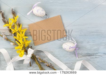 Traditional easter background. Easter eggs willow and forsythia flower with ribbon and blank label on blue wooden background top view.