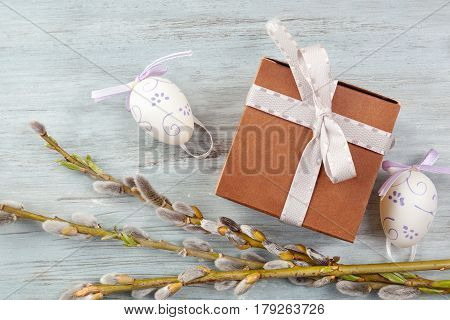 Traditional easter background with gift box with ribbon from above on blue wooden table.