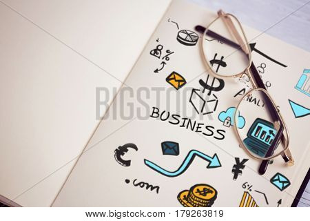 Composite image of various business icons against metallic eyeglasses on wooden table