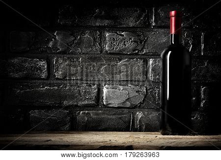 Brick wall in cellar and bottle of cabernet