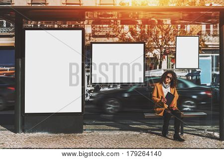 Curly beautiful brunette woman in sunglasses and yellow coat holding digital tablet while sitting and waiting her bus inside of glass city bus stop with several blank mock-up billboards around her