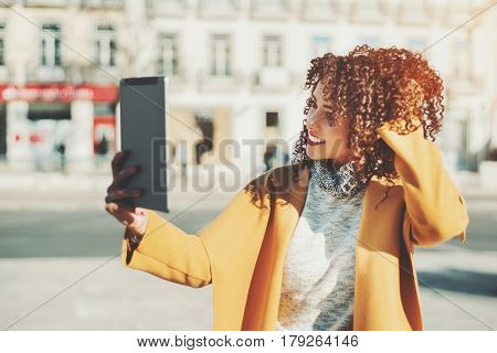 Attractive curly Brazilian woman in yellow coat and sweater having video call using digital tablet adult beautiful smiling lady making selfie on touch pad while standing on city street on sunny day
