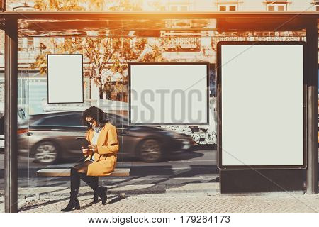 Curly brunette woman in sunglasses and yellow coat working on her digital tablet while sitting and waiting bus inside of glass city bus stop with several blank mock-up banners around her