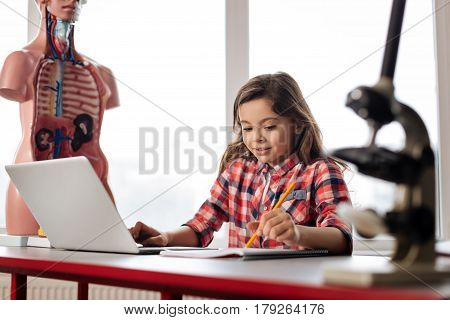 A few pages to go. Enthusiastic attentive persistent student conducting a study on biology while using a laptop and noting down some useful tips